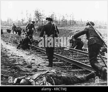 Russian partisans plant mines on a railway line having killed the German sentries whose bodies lie in the foreground - Stock Photo