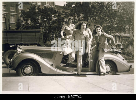 Four glamorous war-time women wearing trouser suits with wide-legged trousers, shirt style blouses & jackets with shoulder pads leap from an open top car. Date: early 1940s