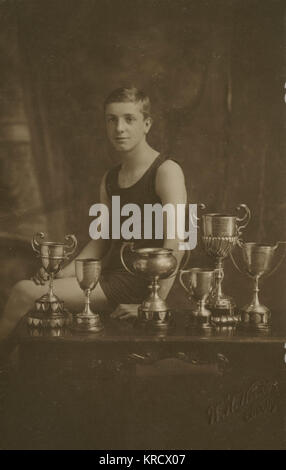 A 14-year-old swimming champion with the six trophies he has won. (2 of 2) Date: 1924 - Stock Photo