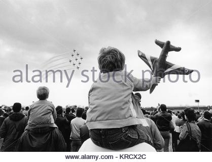 A small boy sits on his fathers shoulders at the Biggin Hill Airshow to get a better view of the Red Arrows. He - Stock Photo