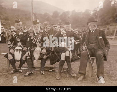 Scene at the annual Braemar Gathering, showing three men in traditional Highland costume and one man in a suit. - Stock Photo