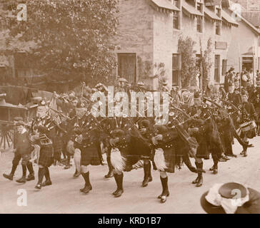 Scene at the annual Braemar Gathering, showing bagpipers in traditional Highland costume processing down a street. - Stock Photo