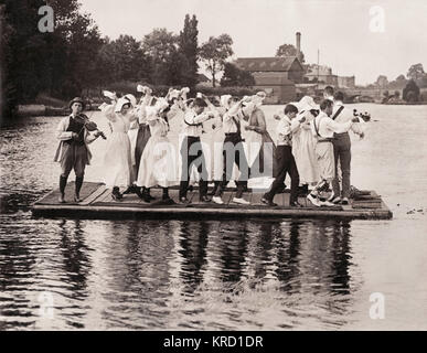 A group of Morris Dancers, male and female, dancing on a floating platform on a river while a violinist provides - Stock Photo