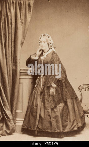 A middle-aged Victorian woman in a dark crinoline dress with a lacy shawl.       Date: 1861
