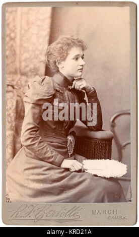 A young Victorian woman poses in the photographer's studio, wearing a stylish dress with a high collar and embroidery on the bodice and cuffs.  She is seated in profile, with a white feather fan in her hand.       Date: circa 1890s