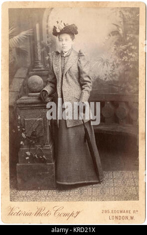 A young Victorian woman in her outdoor clothes poses in the photographer's studio.  She is holding a rolled umbrella in one hand, and leaning on a stone balustrade.      Date: circa 1890s