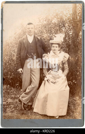 A young Victorian couple pose for their photograph in an outdoor setting.  They are wearing their best clothes, perhaps attending a wedding.      Date: circa 1890s