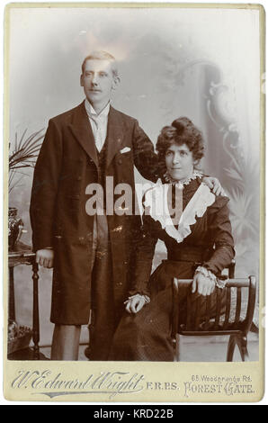 A young Victorian couple pose for their photograph in the studio.  They are wearing their best clothes, perhaps for a wedding.  He wears a long coat, a waistcoat and a wing collar with tie.  She wears a dark dress with lacy white trimmings at the collar and cuffs, and on the bodice.       Date: circa 1890s