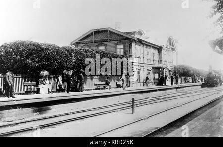 A view of a railway station building and passengers standing on the platform waiting for the approaching steam train, - Stock Photo