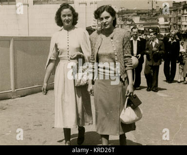 Two female friends walking along the street while on holiday in Blackpool, Lancashire.      Date: early 1950s