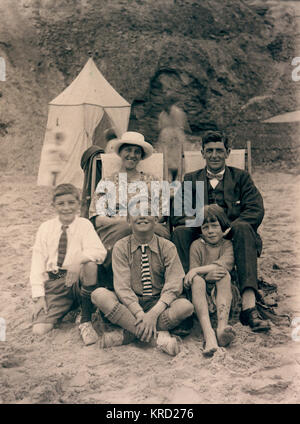 A family of five on holiday.  Mother and father sit on deckchairs in their best clothes, with their three children - Stock Photo