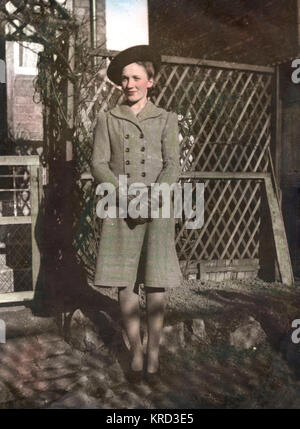 A woman, Dorothy Margaret Hunt (born 1924), poses by a trellis and arch in a garden wearing a typical 1940s skirt suit, with a double-breasted jacket, leather gloves and a hat a jaunty angle.       Date: c.1944