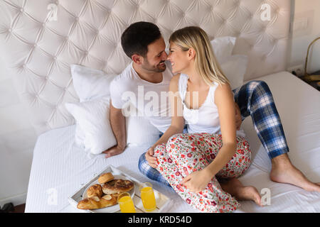 Couple kissing and having breakfast in bed. - Stock Photo