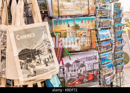 Decorative tourist bags, pictures and postcards on display at a souvenir stall in Cannes, Cote D'Azur, South of - Stock Photo