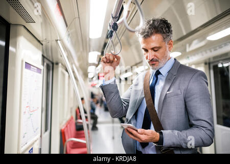 Mature businessman with smartphone in a metro train. - Stock Photo