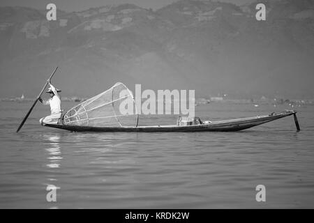 Traditional fisherman with net on a long boat  Inle Lake, Myanmar, South East Asia - Stock Photo