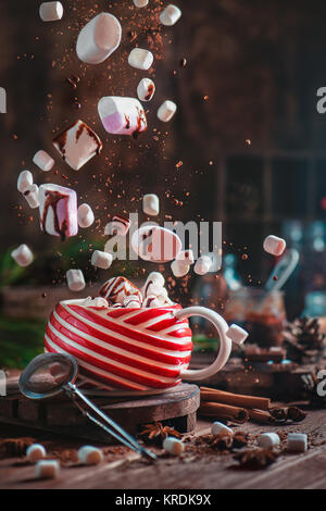 Christmas hot cocoa with flying marshmallows and chocolate. New Year celebration scene with chocolate crumbs, spices - Stock Photo