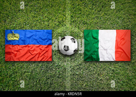 Liechtenstein vs. Italy flags on soccer field - Stock Photo