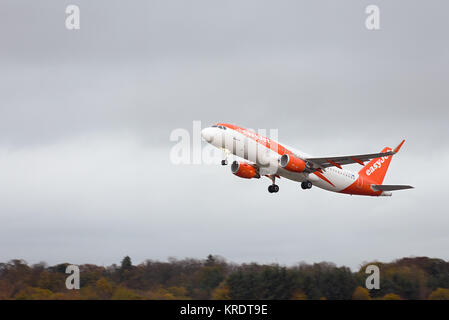 EasyJet passenger airplane G-EZPN Airbus A320-214 in flight after taking off with wheels down at Edinburgh International - Stock Photo