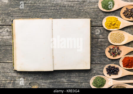 Blank recipe book and spices in wooden spoons. - Stock Photo