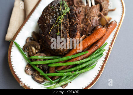 Close up shot of a pot roast with carrots, green beans and mushrooms on a white platter with gold rim.