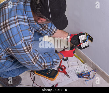 The technician wears the normal protective devices. Electrician's hands assembles a standard bipolar wall socket. - Stock Photo