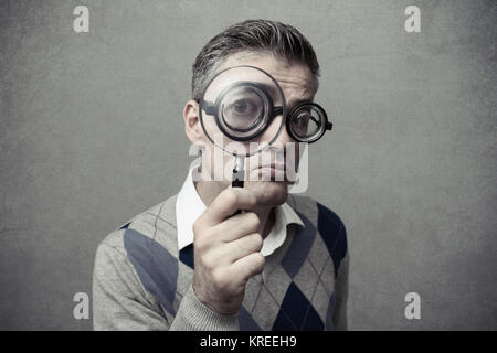 Nerd guy looking through a magnifying glass with a clueless expression - Stock Photo