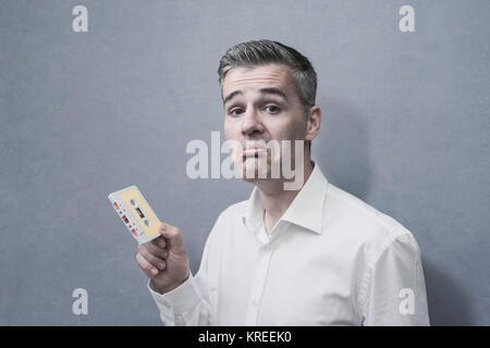 Clueless confused man holding an old audio cassette, vintage outdated technology concept - Stock Photo