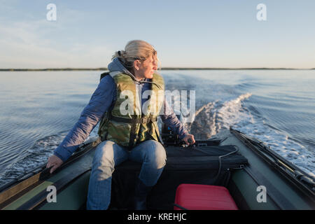 Beautiful woman is operating of boat on the sea - Stock Photo