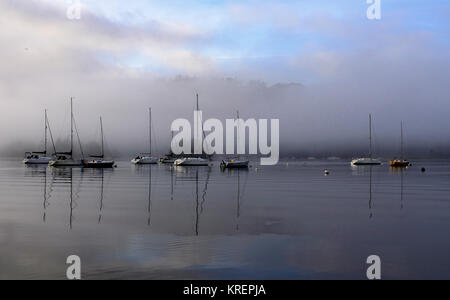 Boats on Windermere as the early morning mist starts to lift. - Stock Photo