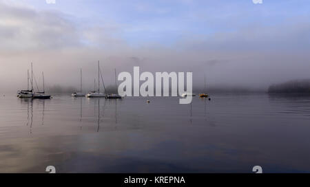 Boats on Windermere as the sun starts to lift the early morning mist - Stock Photo