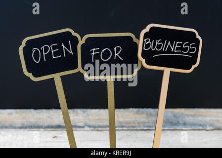 OPEN FOR BUSINESS message written with chalk on wooden mini blackboard labels - Stock Photo