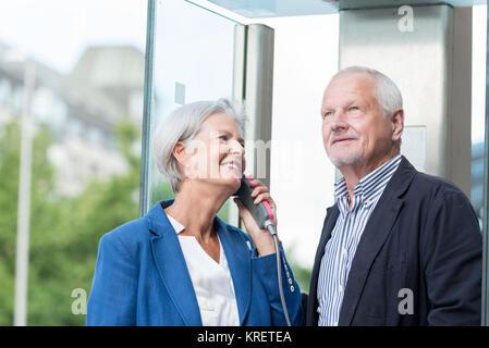 Zwei Senioren stehen an einer öffentlichen Telefonzelle und telefonieren - Stock Photo