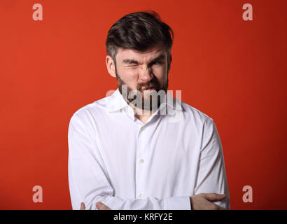 Grimacing emotional disgasted bearded business man looking unhappy in white style shirt. Closeup portrait on bright - Stock Photo