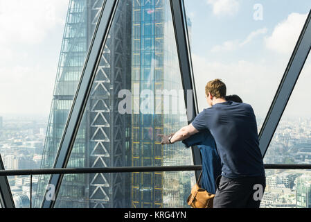 Couple enjoying the view of the city of London with the Leadenhall Building in the front. Taken from the rooftop - Stock Photo