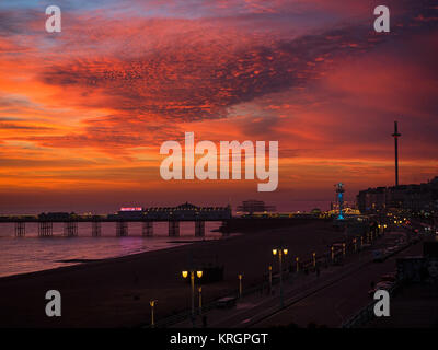 Intense sunset on Brighton seafront, showing the i360, West Pier with a murmuration of starlings, Palace Pier and - Stock Photo