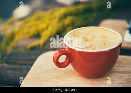Red coffee cup in a summer day with flowers in background - Stock Photo