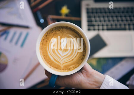 Coffee in focus and work office background - Stock Photo