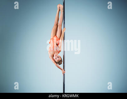 The strong and graceful young girl performing acrobatic exercises on pylon - Stock Photo