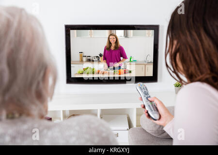 Two Women Watching Cooking Show On Television - Stock Photo