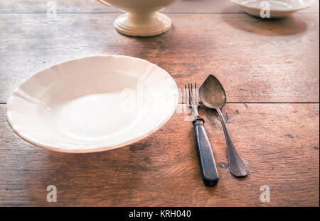 Antique plate and tableware on aged wooden table - Stock Photo