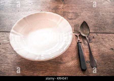 Rustic weathered tableware on wooden table - Stock Photo