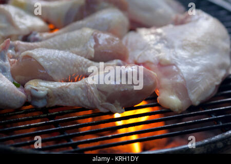 Cooking chicken drumsticks, thighs and wings on the grill. - Stock Photo