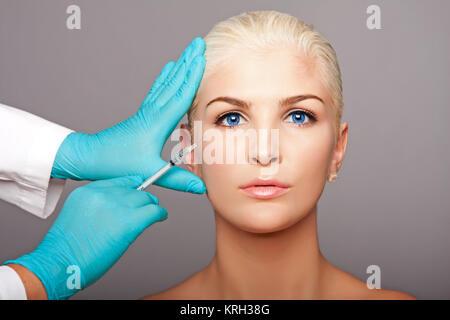 Cosmetic plastic surgeon injecting aesthetics face - Stock Photo