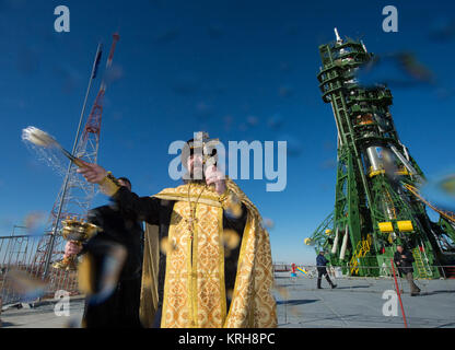 An Orthodox priest blesses members of the media at the Baikonur Cosmodrome launch pad on Saturday, Nov. 22, 2014, - Stock Photo