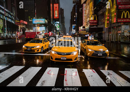 New York Medallion Yellow Taxi Cabs Line up at crossing on a rainy evening in Time's Square, New York City, America - Stock Photo