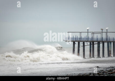 Storm waves on the sea are broken about the pier. - Stock Photo
