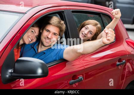 Family Sitting In Car Raising Their Arms