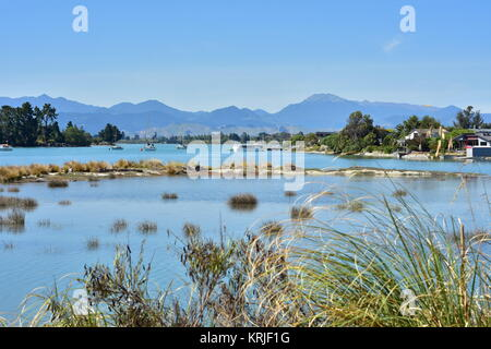 Shallow estuary with recreational vessels anchored on calm water and hills in background. - Stock Photo