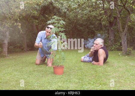 Seniors smoking marijuana and relaxing in the garden - Stock Photo